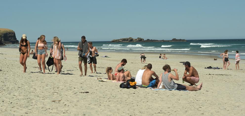 People enjoy the sun at Tomahawk Beach last month. Photo: Linda Robertson