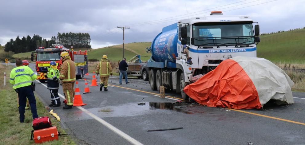 紧急服务工作在化粪池车和附近的汽车发生碰撞现场......