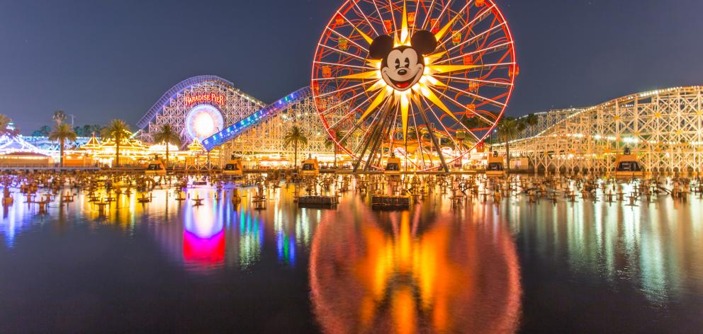 People walk around rides and games at Cars Land during a night session at Disneyland. PHOTOS:...