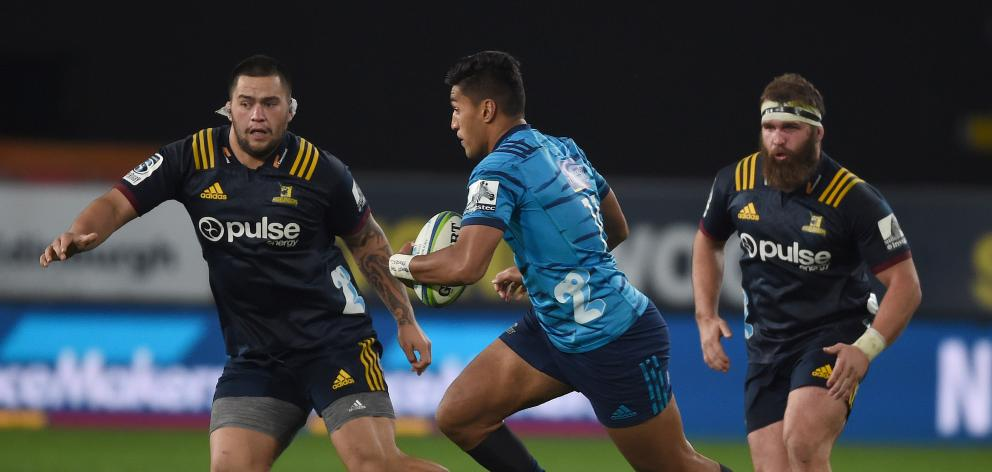 Blues winger Rieko Ioane attempts to get away from Highlanders front rowers Tyrel Lomax (left)...