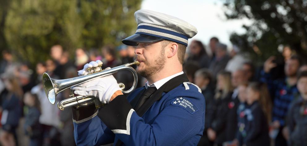 Kaikorai Metropolitan Brass cornettist Mat Patchett plays Last Post and Reveille while posies...