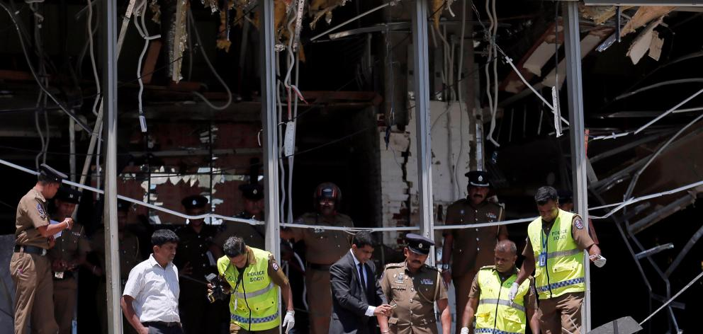Crime scene officials inspect the explosion area at Shangri-La hotel in Colombo. Photo: Reuters