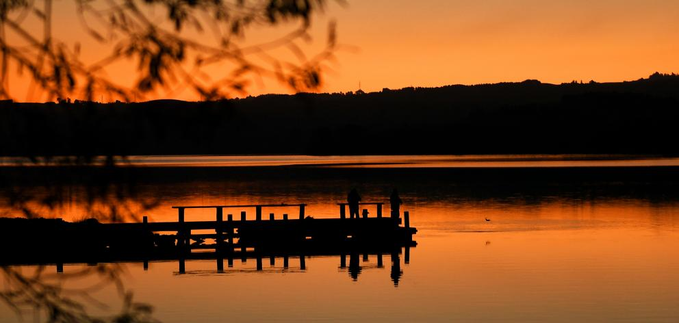 Fishermen hook their quarry under the glow of the setting sun at Lake Waihola yesterday. PHOTO:...