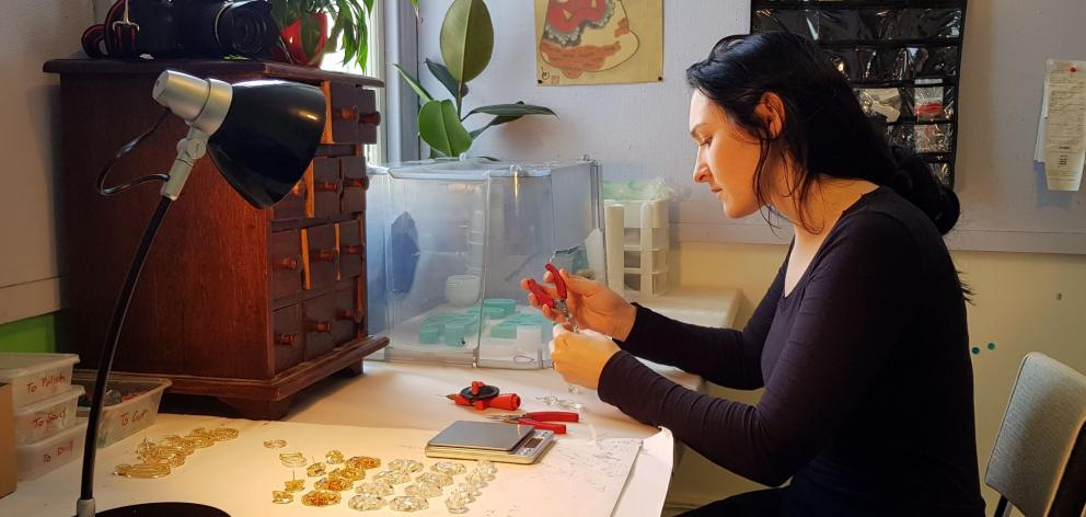 Little Constellation jewellery designer Maria Brett works on a pair of handcrafted earrings in...