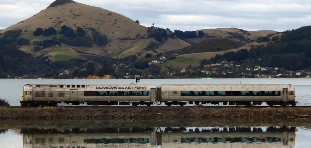 Dunedin's Silver Fern rail car crosses the causeway at Blanket Bay, with Otago Peninsula's...