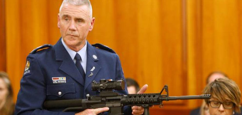 Police Senior Sergeant Paddy Hannan shows lawmakers in Wellington an AR-15 style rifle similar to one of the weapons allegedly used in the mosque attacks. Photo: AP