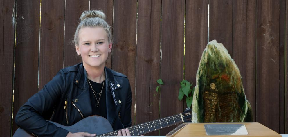 Musician Casey Dixon, of Kenmure, at home on Tuesday with her trophy for winning the supreme senior overall prize at the Southern Alps Country Music Awards. Photo: Shawn McAvinue