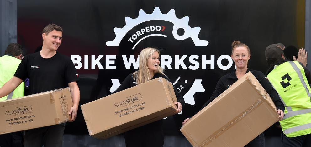 Torpedo7 staff at the Andersons Bay Rd outlet (from left) bike mechanic Sebastien Bossard and sales team members Sophie Letcher and Carole McCaughan move goods while, in the background, workmen affix new signs. Photo: Peter McIntosh