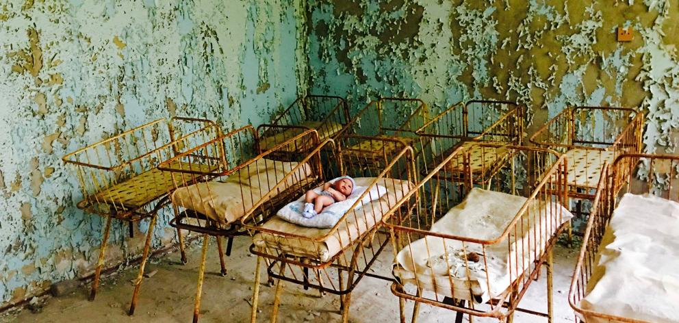 A rusting cot containing a baby doll and blanket sits in the Pripyat hospital maternity ward.