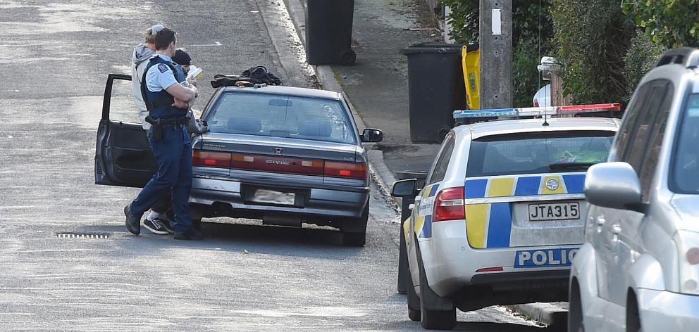 Police search a car parked in Craigleith St yesterday afternoon after reports of a group of men...