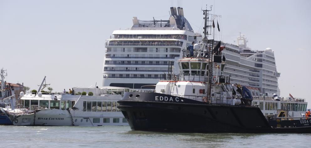 The towering cruise ship MSC Opera has struck a dock and a tourist river boat on a busy canal in...