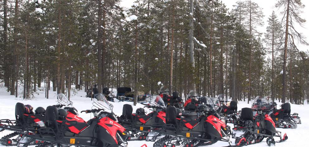 Snowmobiles on the edge of frozen Pikku-Mellalampi Lake.