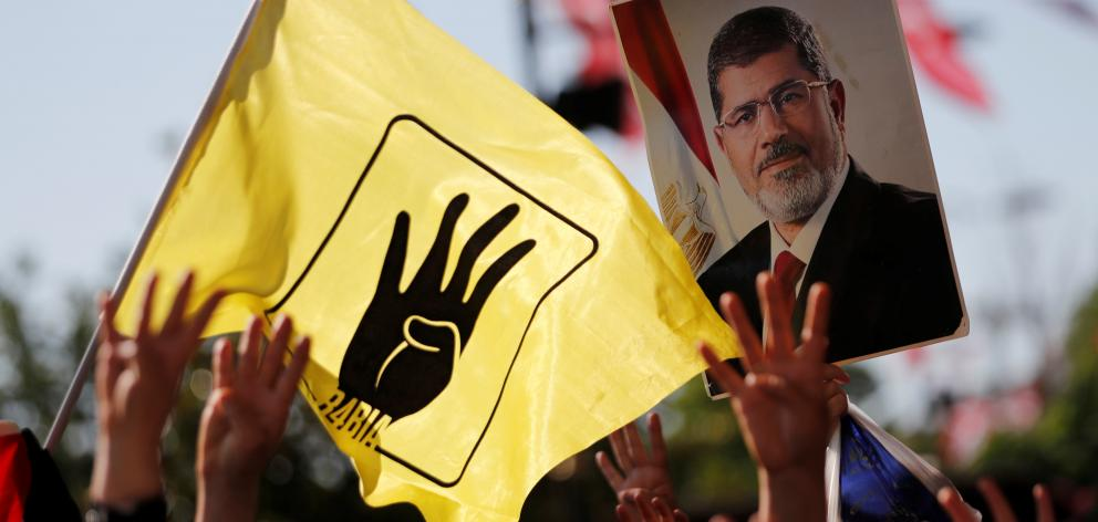 NO ARCHIVEPeople flash Rabia signs as they hold a picture of former Egyptian president Mursi during a symbolic funeral prayer in Istanbul. Photo: Reuters