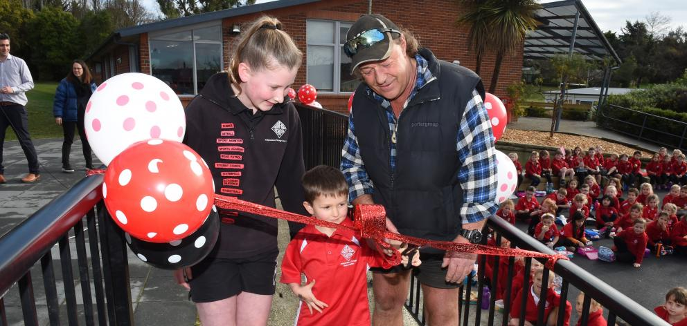 Fairfield school pupils Charly Wood (13) and Declan Wright (5) cut a ribbon with board of trustees chairman Greg Inch, to open the school's new play area. Photo: Gregor Richardson