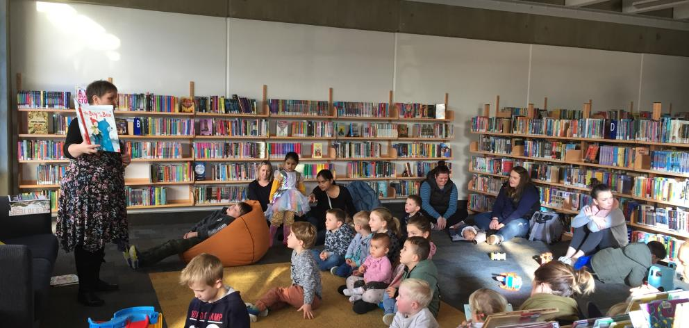After power was cut to most of the city centre, staff at the Invercargill City Library had to improvise and move a school holiday reading session closer to the windows. Photo: Luisa Girao
