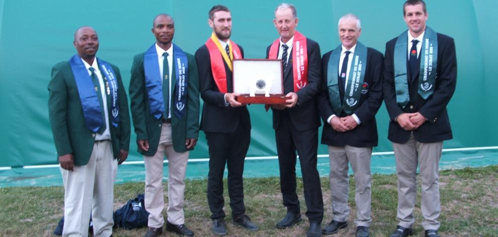 Geraldine's Allan Oldfield, and Fairlie's Tony Dobbs hold the team's world championship trophy. At the left are runners-up Mayenseke Shweni and Bonile Rabile, of South Africa, and, on the right, English father and son team, George and Andrew Mudge. Photo: