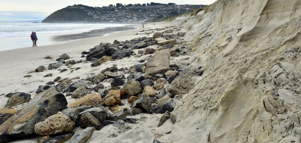 Exposed pieces of rock, concrete, brick and other rubble lie on the sand at Dunedin's Ocean Beach...