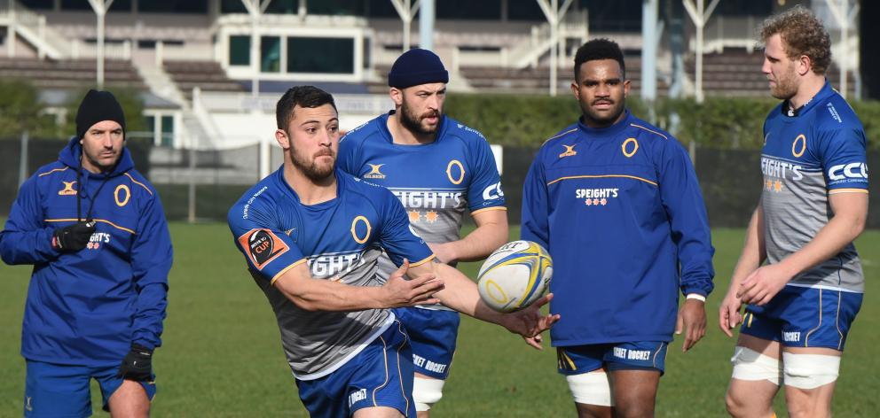 Otago midfield back Aleki Morris looks to move the ball on under the watchful eye of (from left)...