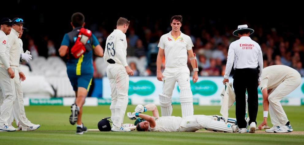 ustralia's Steve Smith lays on the floor after being hit by a ball from England's Jofra Archer as England's Jos Buttler and Australia's Pat Cummins look on. Photo: Action Images via Reuters