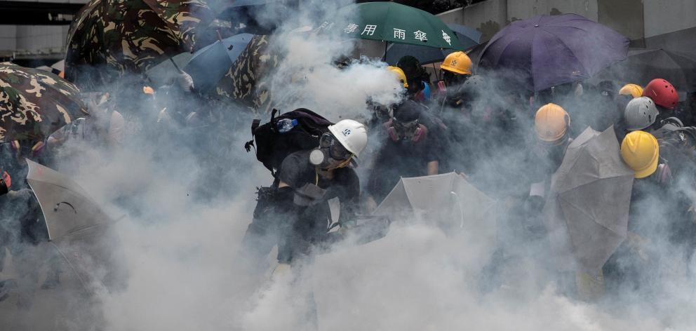 Demonstrators take cover as police fires tear gas during a protest in Hong Kong on Saturday....