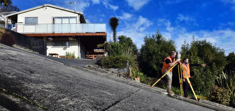 Dunedin surveyors Dylan Hills (left) and Toby Stoff start creating a super-accurate model of Baldwin St as part of their battle against Guinness World Records to reclaim the street's crown as the world's steepest. Photo: Peter McIntosh