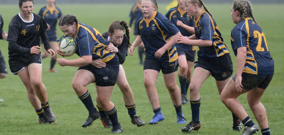 Taieri College player Ruby Walpole has plenty of support as she tries to get past the defence of...