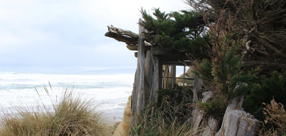 Perched on the edge of the cliff-face at Gemstone Beach in Southland is the shell of a house....
