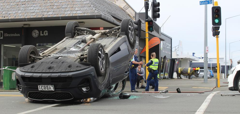A car was left on its roof in a three-vehicle crash at an Invercargill intersection yesterday....