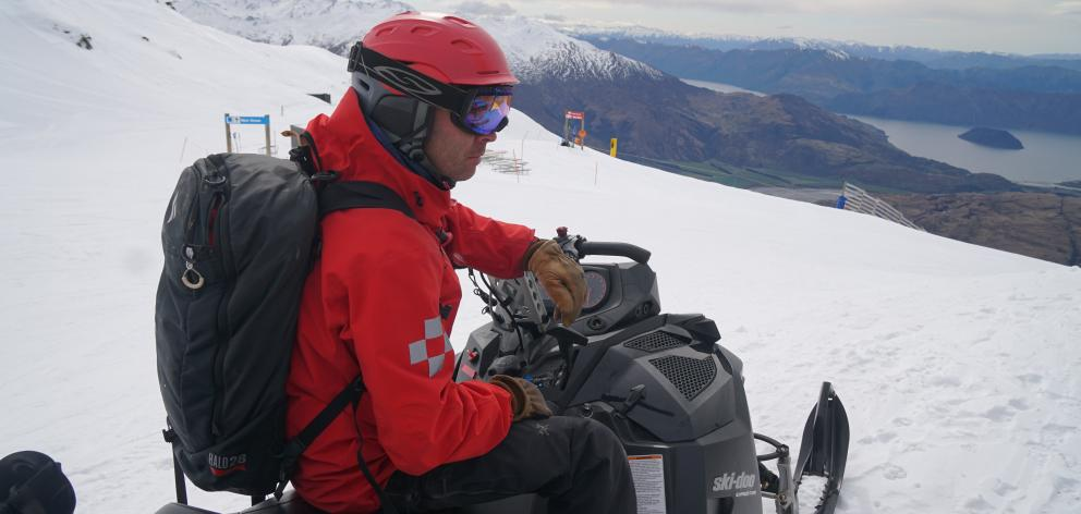 Treble Cone skifield patroller Erik Besselman carrying a backpack of explosives to trigger any...