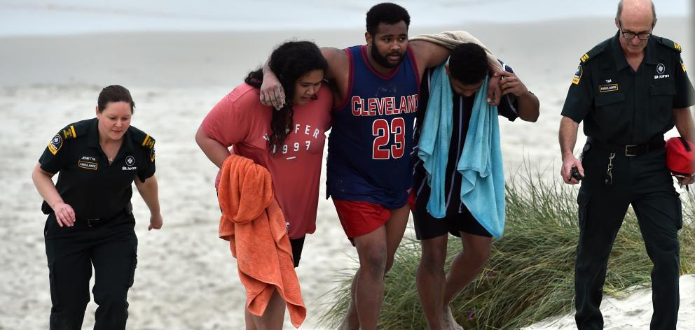 Lua Rasmussen (second left) helps Mosese Dolodolotawake (centre) ashore after the pair were among...