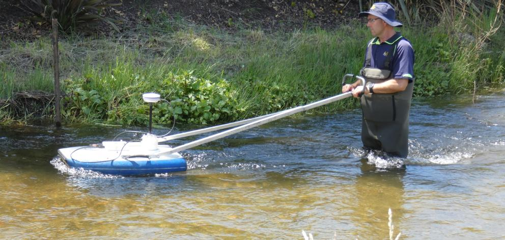 Otago Regional Council environmental officer Mike Anderson floats a boogie board loaded with data...