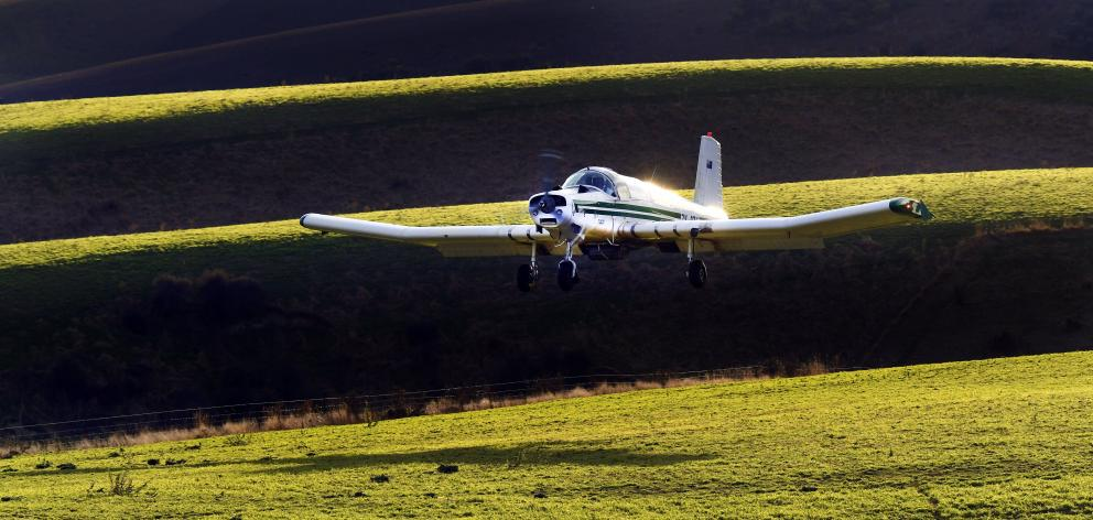 A topdressing plane applies a load of fertiliser on to a Central Otago property. PHOTO: STEPHEN...