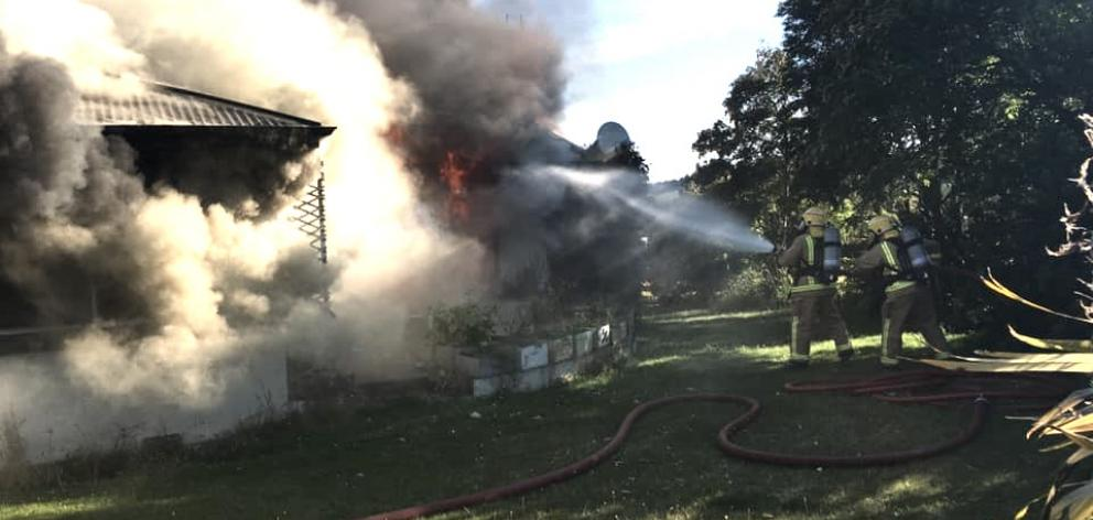 Volunteer firefighters tackle a house fire near Te Anau yesterday. Photo: Te Anau Volunteer Fire Brigade