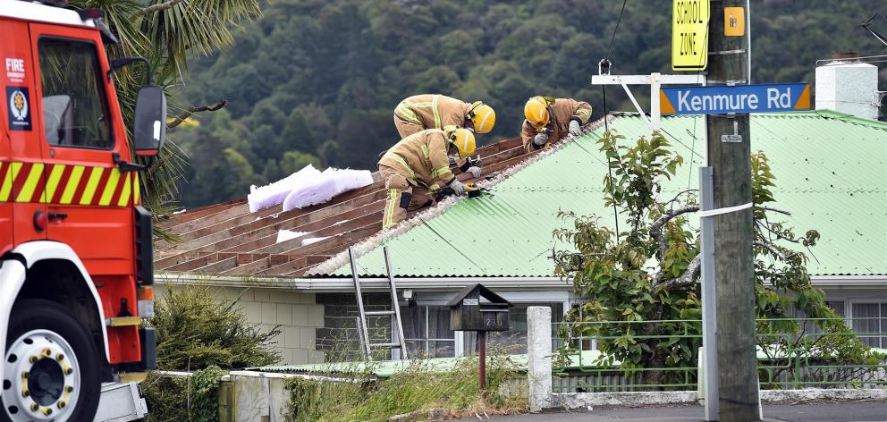 Part of Kenmure Rd, in Dunedin, was closed for a time late this afternoon, when roofing iron was blown from a house into neighbouring properties and across the road. PHOTO: PETER MCINTOSH