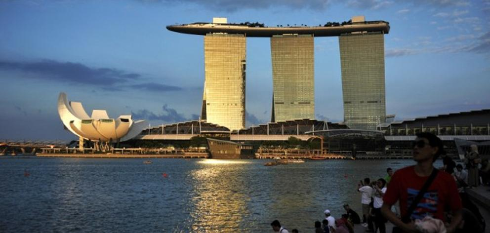 eople sit on the waterfront as sunlight shines on the Marina Bay Sands resort in Singapore. Photo: Reuters