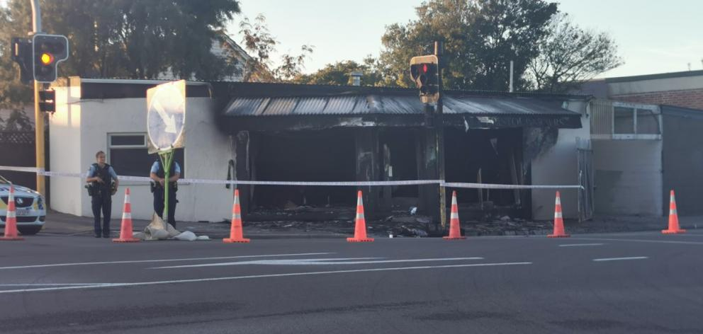 Police stand guard on Monday morning after the fire at Bristol Barbers on Wainoni Rd. Photo: Ian...
