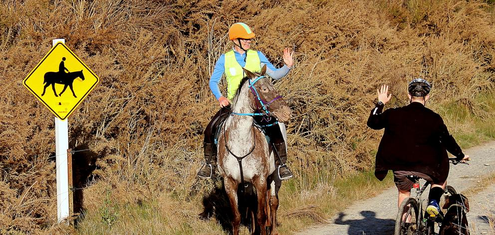 Brenda Reading greets a cyclist as she rides along part of the old Waitaki Haul Rd. Photo: Supplied