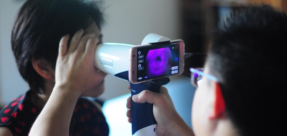 Dr Hong Sheng Chiong checks the retina of a farm worker at Batu Kawa, Kuching, in Sarawak. PHOTO:...
