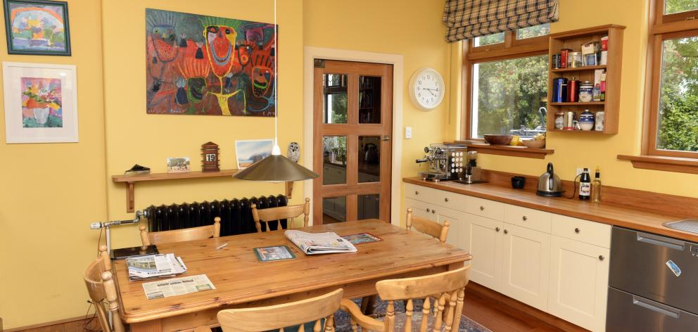 The kitchen was expanded by removing a servery between it and the dining room. The large painting...