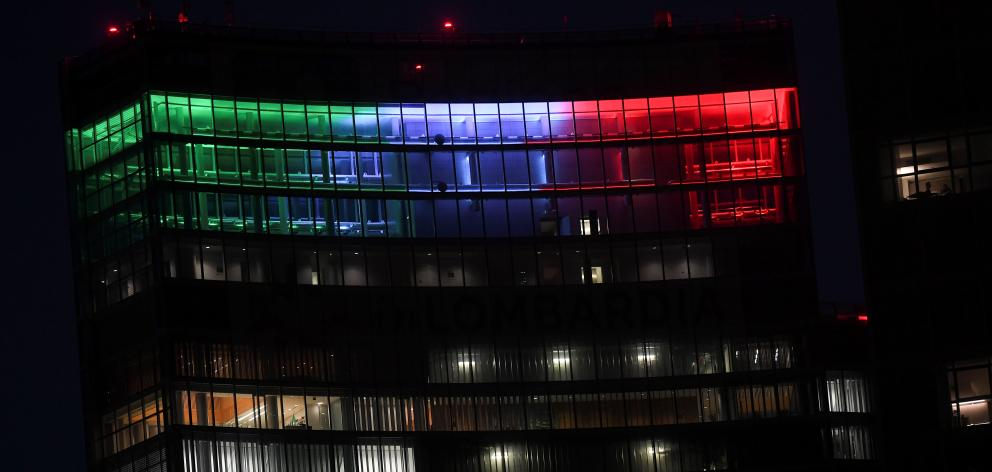 The Palazzo Lombardia building is seen iluminated with the colours of the Italian flag in Milan. Photo: Reuters