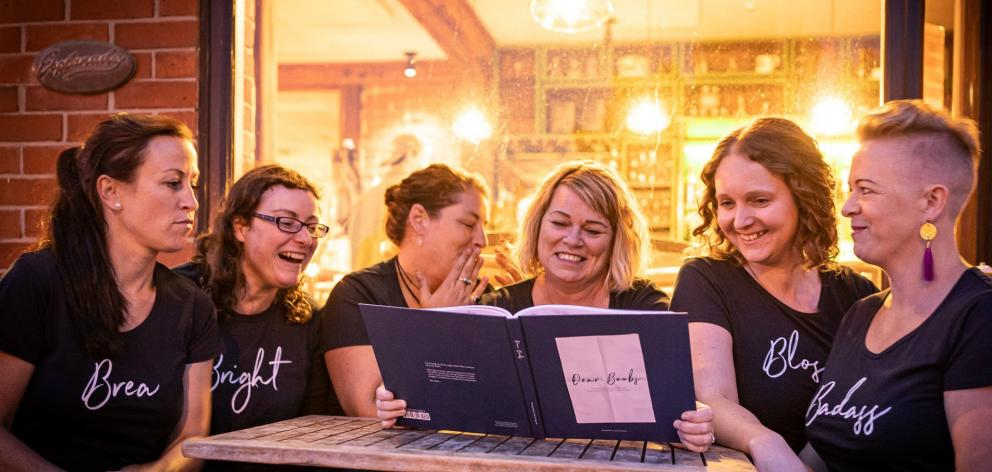 Actors (from left) Denise Casey, Kimberley Buchan, Marama Grant, Lesley Eaton, Helen Fearnley and Harriet Moir take a look at the book that inspired Dear Boobs on Stage. Photo: Nick Beadle