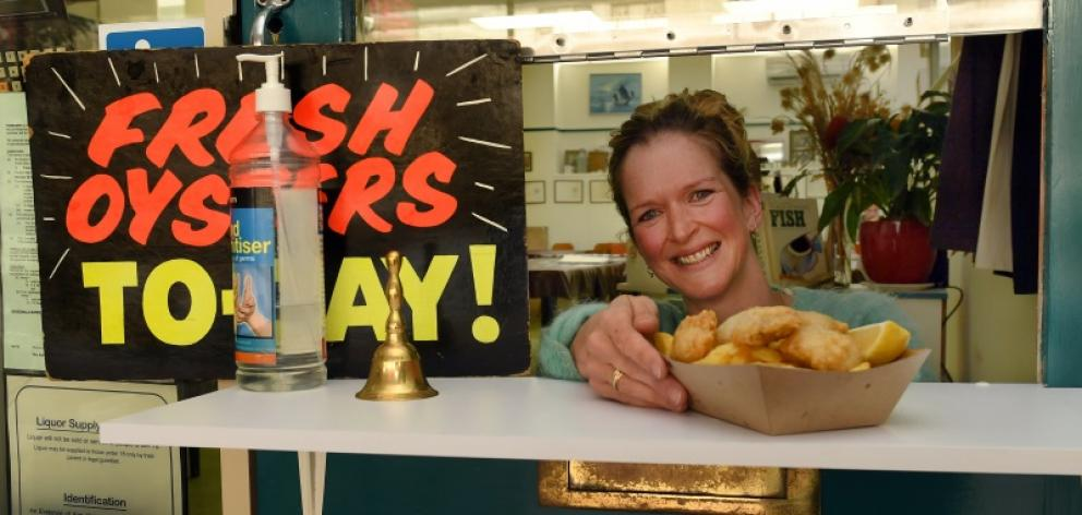 Order up ... Best Cafe owner Jessica Marks serves takeaway orders to a customer yesterday while...