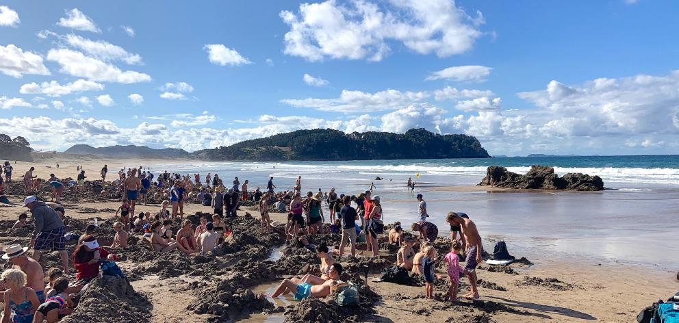 Hot Water Beach on a summer's day  with bathers enjoying geothermally  heated water.