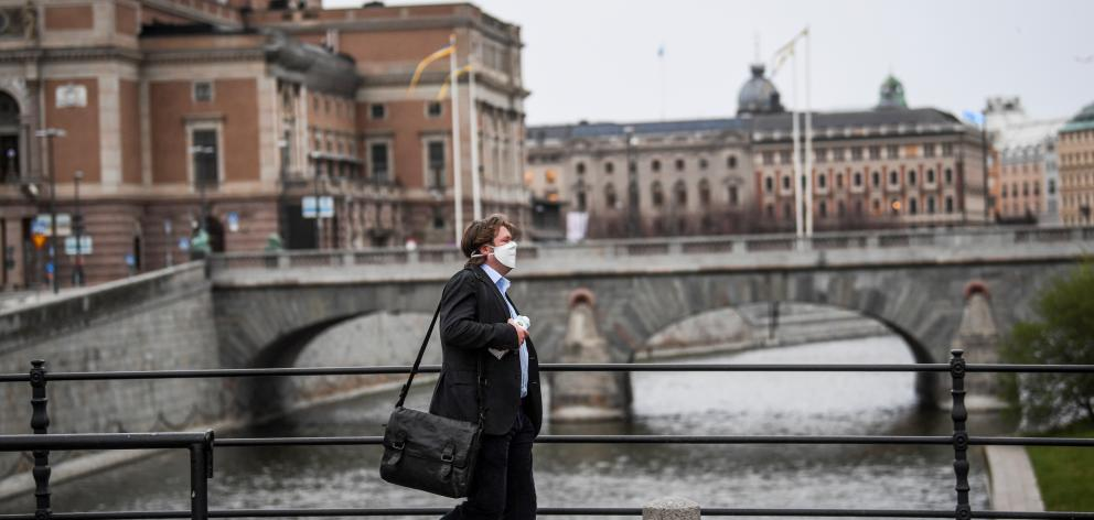 A man wearing a protective mask walks past the Royal Swedish Opera, amid the Covid-19 outbreak in Stockholm. Photo: Reuters