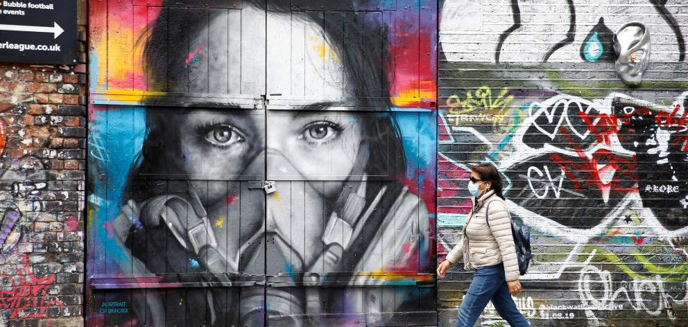 A woman wearing a protective face mask walks past streetart in Shoreditch following the outbreak of the coronavirus disease (COVID-19), London Reuters