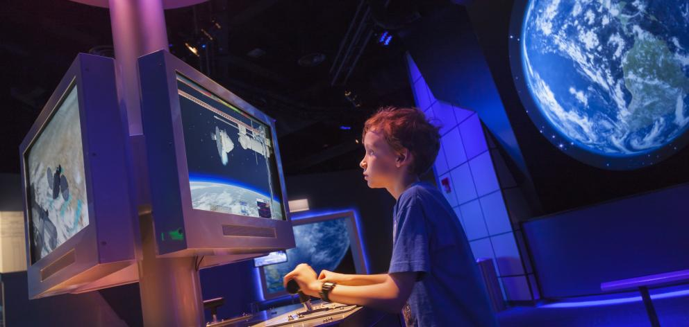 A young boy using a simulator at the Visitors Complex at the Kennedy 