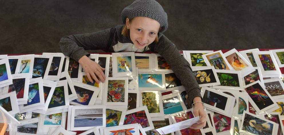 Taking a moment to look at Ian Marechal's photocards on display, Madeleine Cumberpatch (11), of...