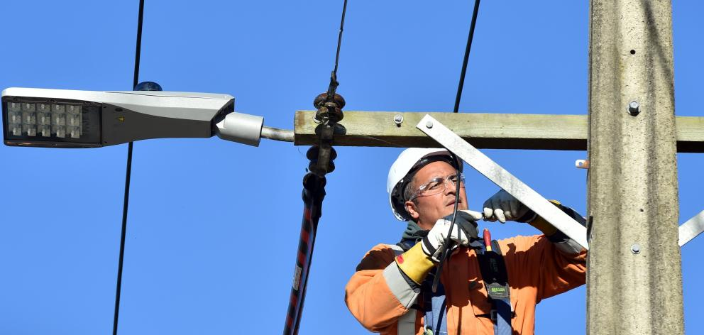 Installing a new LED street light in Stevenson Rd, Concord, yesterday, is Broadspectrum employee...