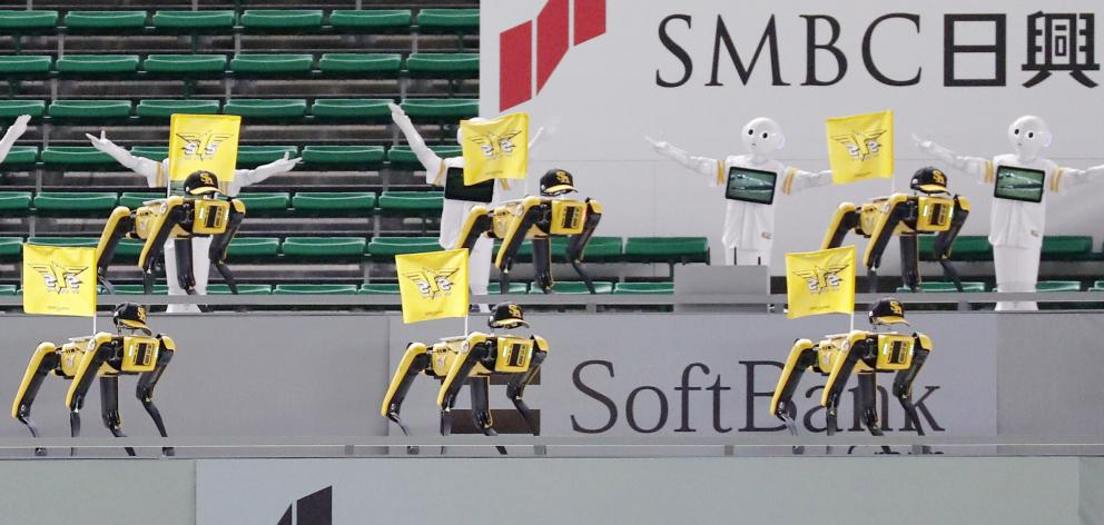 Robots cheer the team next to empty spectator seats at a baseball game between SoftBank Hawks and Tohoku Rakuten Golden Eagles in Fukuoka, Japan. Photo: Kyodo/via Reuters