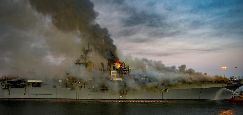 Boats combat a fire on board the US Navy amphibious assault ship USS Bonhomme Richard. Photo: U.S. Navy/Mass Communication Specialist 2nd Class Austin Haist/Handout via Reuters
